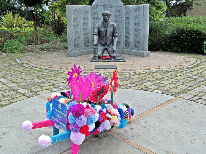 Westhoughton Yarn Bombing Festival 2nd / 3rd July 2016 - St. Bart's Primary School wheel barrow display, with Pretoria Disaster statue at Ditchfield Gardens